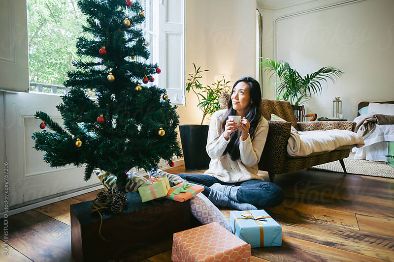 Asian woman looking the Christmas tree at home. by BONNINSTUDIO for Stocksy United