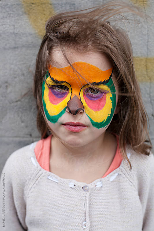 young girl with face painted as an owl for Halloween by Natalie JEFFCOTT for Stocksy United