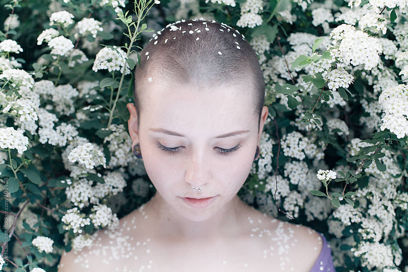 A girl with a shaved head and flowers by Erik Naumann for Stocksy United