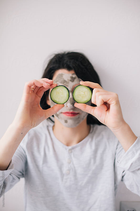 Woman with home made facial mask holding slices of cucumber in front of her by Marija Mandic for Stocksy United