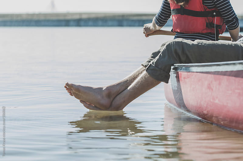 Man's Feet in the Water by Tomas Kraus for Stocksy United
