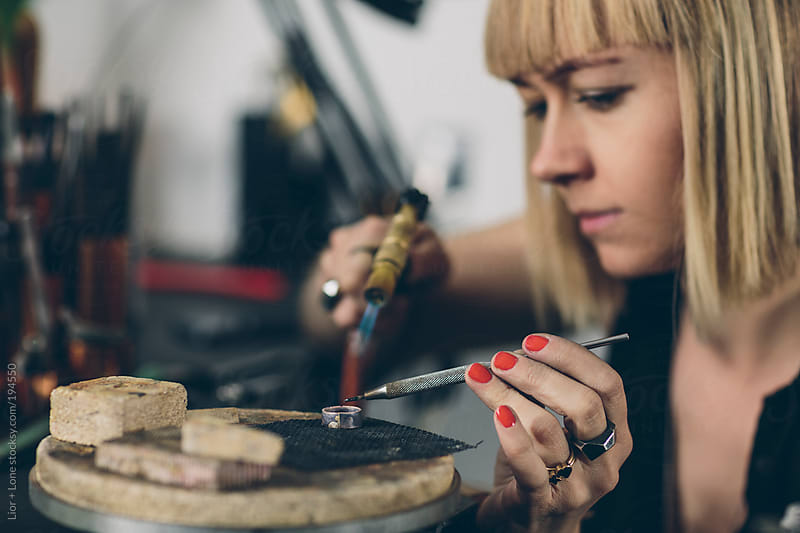 Young attractive jewelry designer working on a piece in her workshop by Lior + Lone for Stocksy United