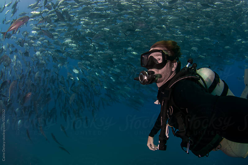 SCuba diver takes selfie surrounded by thousands of fish by Caine Delacy for Stocksy United