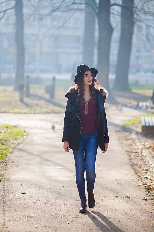 Young beautiful woman with black curly hair and red lipstick walking in the city park by Maja Topcagic for Stocksy United