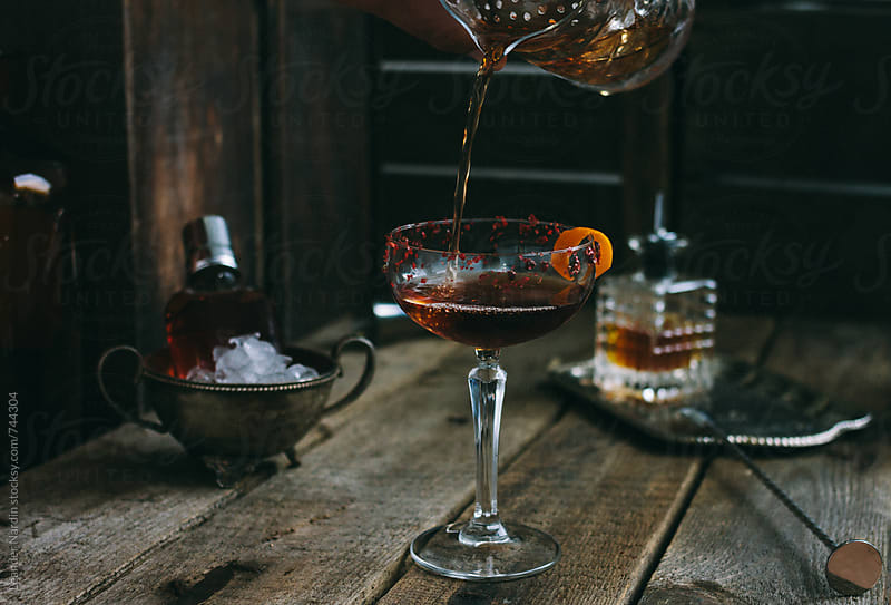 classic manhattan cocktail pouring into a champagne saucer - coupette by Leander Nardin for Stocksy United
