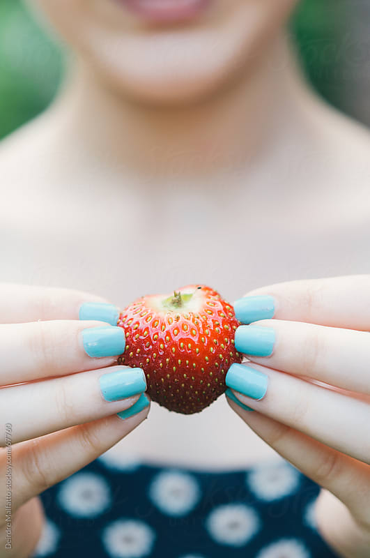 Girl with blue nailpolish holding red strawberry by Deirdre Malfatto for Stocksy United