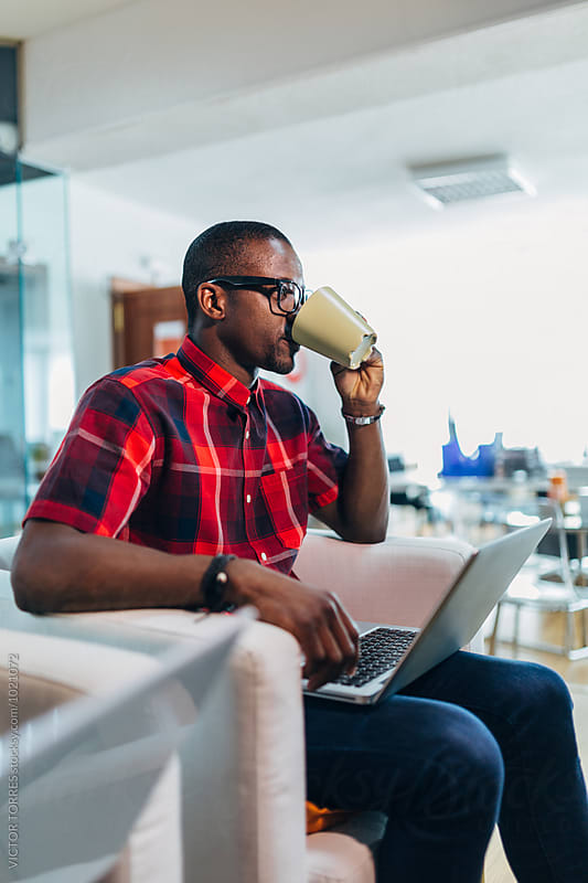 Young African Businessman Drinking a Coffee at the Office