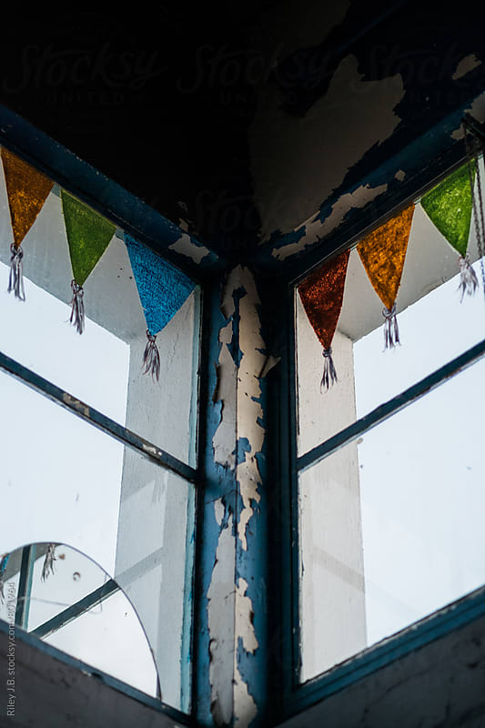 Coloured pennants line the top of windows in an old, derelict building. by Riley J.B. for Stocksy United