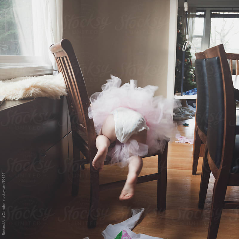 Cute toddler in tutu climbs chair by Rob and Julia Campbell for Stocksy United