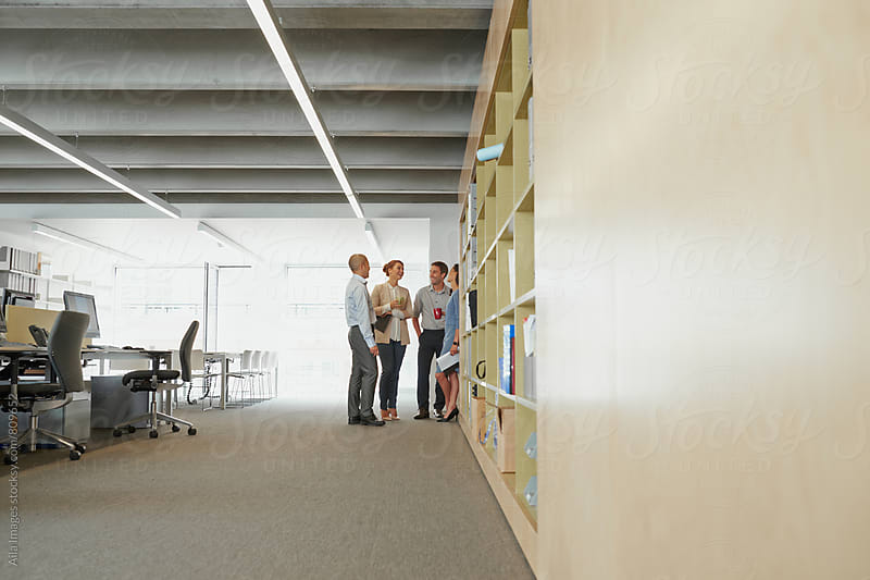 Informal business meeting in empty office happy businessmen businesswoman smiling laughing at work by Aila Images for Stocksy United