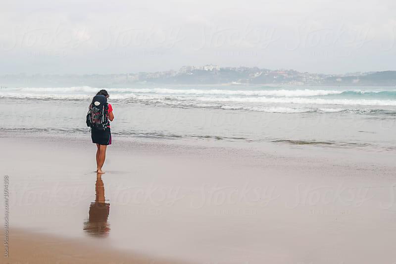 Female hiker walking barefoot on the beach by Luca Pierro for Stocksy United
