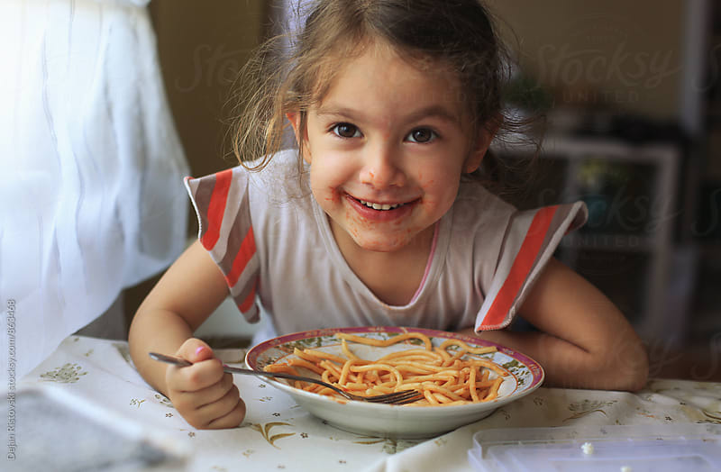 Sweet girl eating spaghetti. by Dejan Ristovski for Stocksy United