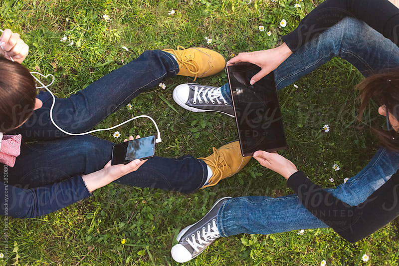 Friends using smartphone and a tablet by Jelena Jojic Tomic for Stocksy United
