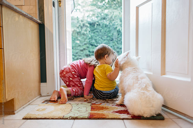 Two children petting a dog by a door by Jakob for Stocksy United