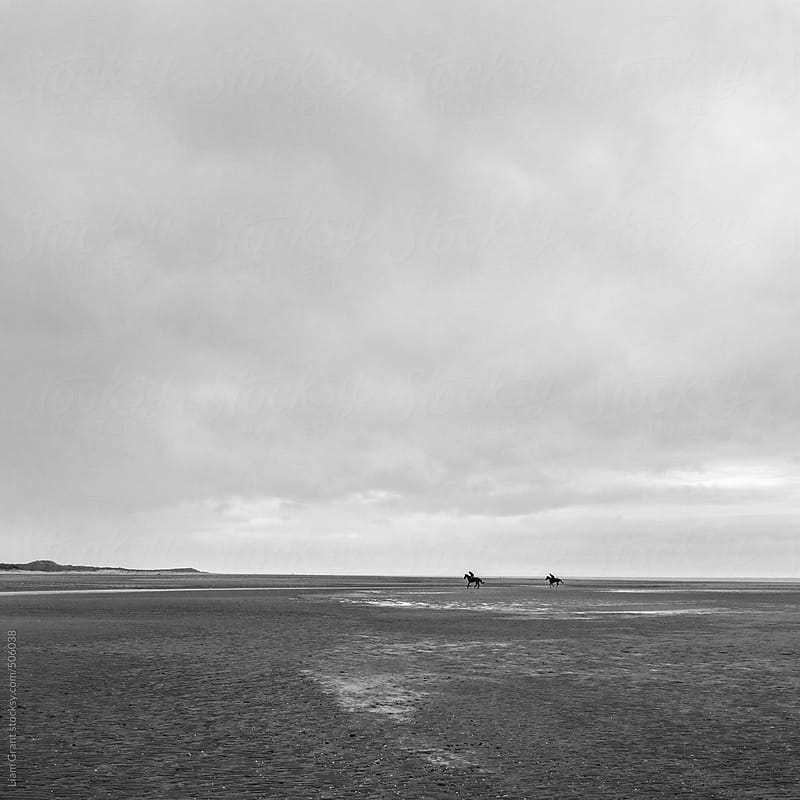 Two horses and riders on an empty beech. by Liam Grant for Stocksy United
