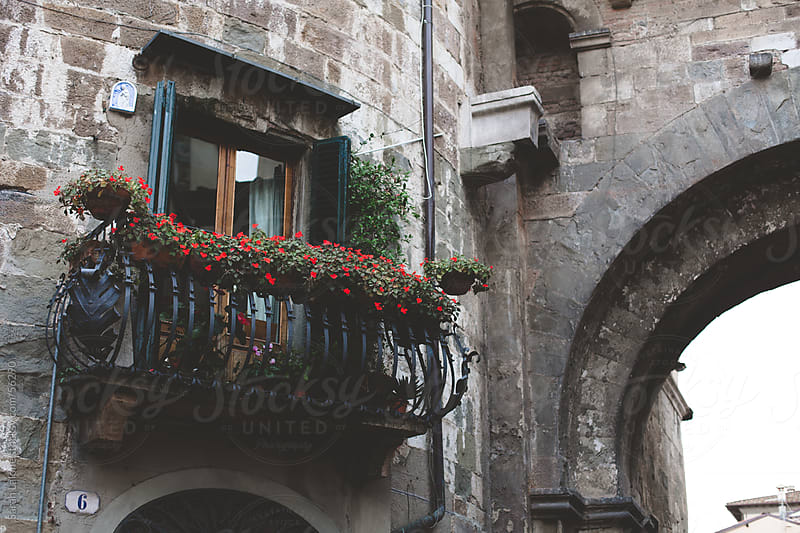 Window with flowers in a stone building in Italy by Sarah Lalone for Stocksy United