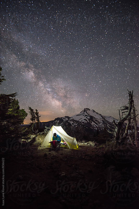 Man in tent in front of Mt Jefferson with starry night sky by Isaac Lane Koval for Stocksy United