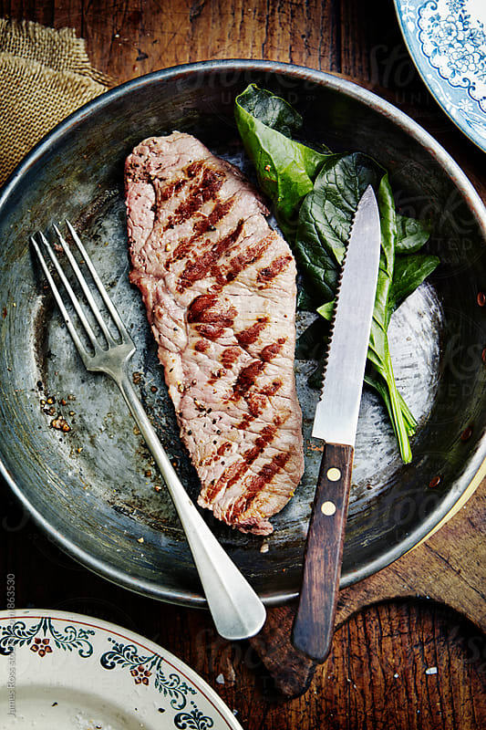 A cooked steak with spinach leaves in a pan by James Ross for Stocksy United