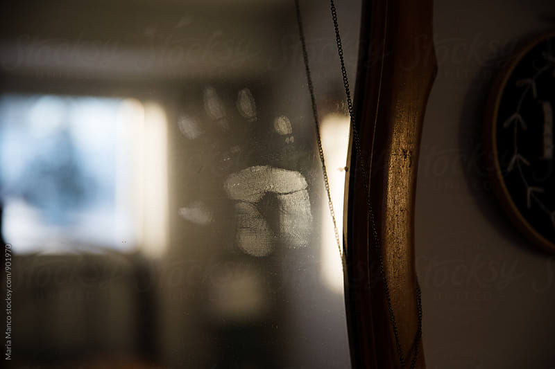 Close up of child's handprint on a mirror by Maria Manco for Stocksy United