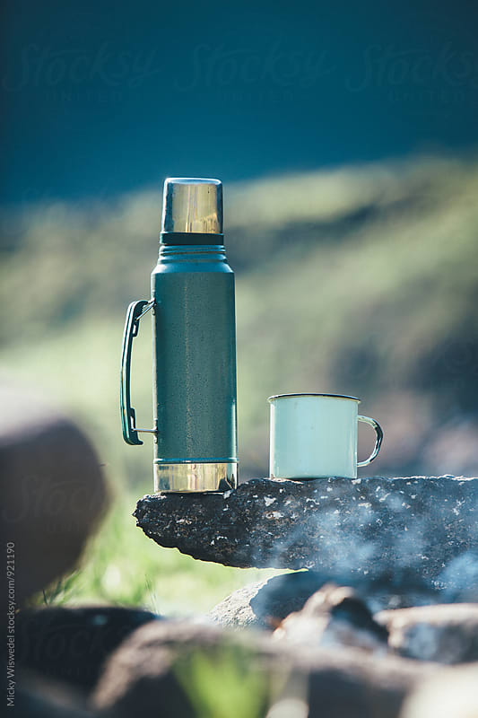 thermos flask and mug on a rock by a smouldering fire by Micky Wiswedel for Stocksy United