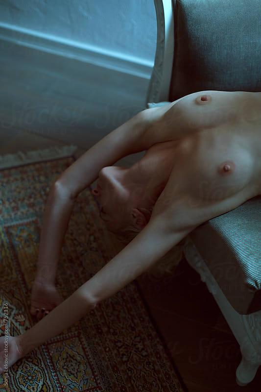 naked woman lying on the sofa by Sonja Lekovic for Stocksy United