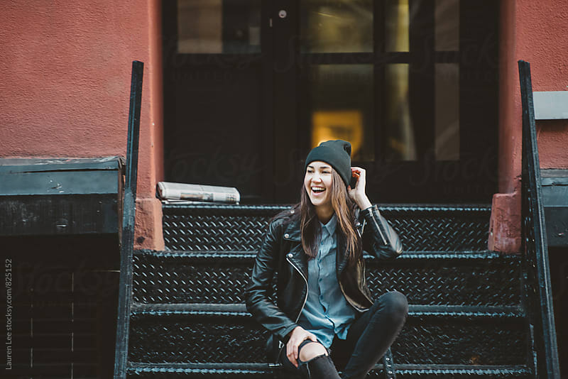 Happy young woman sitting on stoop in the city by Lauren Naefe for Stocksy United