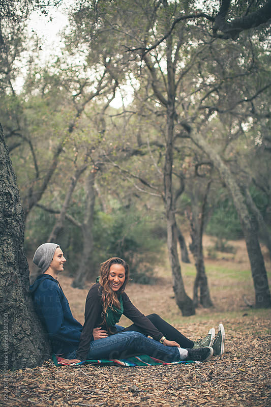 Attractive young couple sitting against a tree.  by RZ CREATIVE for Stocksy United