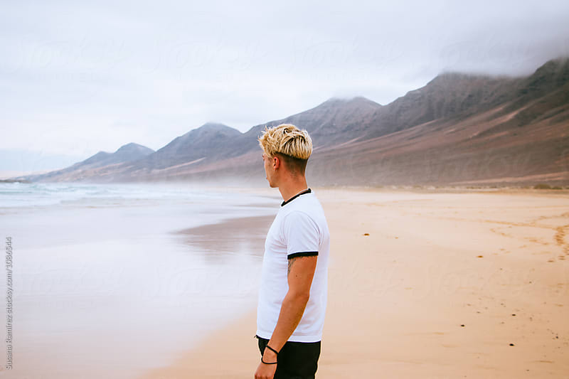 Young man on the beach looking out to sea by Susana Ramírez for Stocksy United