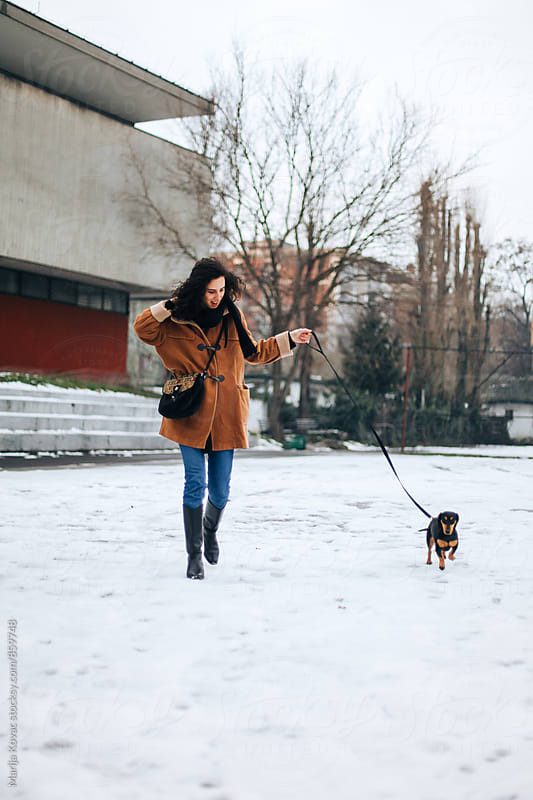 Happy woman having fun with her dog on a winter day by Marija Kovac for Stocksy United