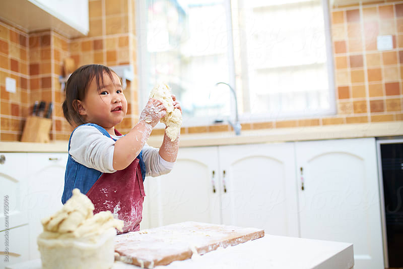 little asian girl working with flour in the kitchen by Bo Bo for Stocksy United