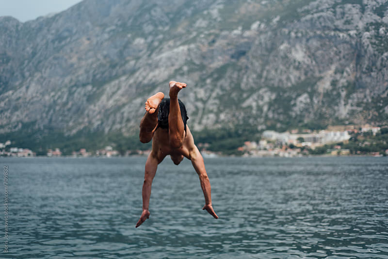 Muscular man jumping in the water by Boris Jovanovic for Stocksy United