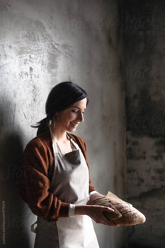Smiling Woman Holding a Loaf of Bread by Lumina for Stocksy United