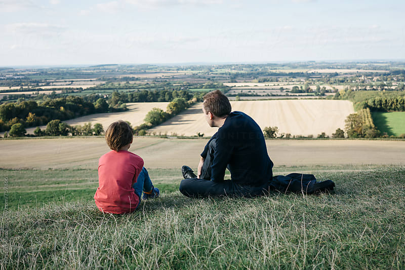 Father and son looking out over view in Oxfordshire by Kirstin Mckee for Stocksy United