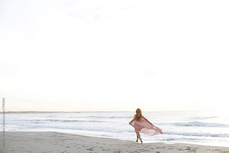 Woman running along beach  by Jennifer Brister for Stocksy United