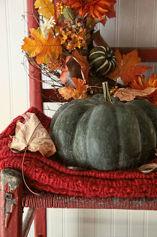 Green pumpkin on old red chair by Sandra Cunningham for Stocksy United