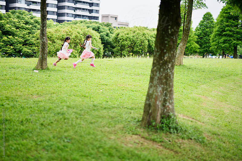 Two girls in pink running on park lawn by Lawren Lu for Stocksy United