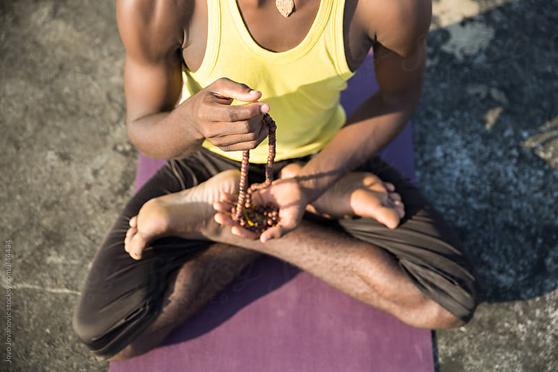 Closeup of a dark skinned male meditating in a lotus yoga pose by Jovo Jovanovic for Stocksy United