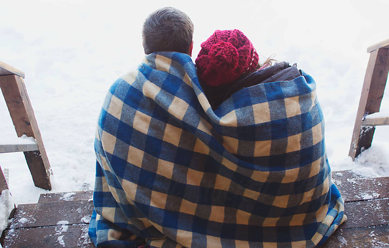 couple cuddled together under blanket sitting on porch on winter day by Tana Teel for Stocksy United