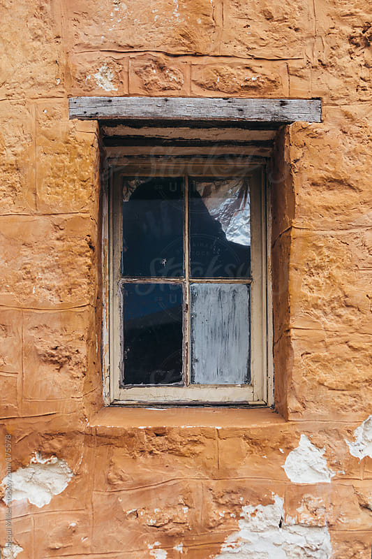 Old window in an orange wall by Jacqui Miller for Stocksy United