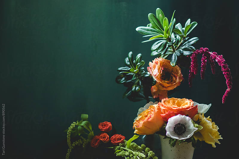 Colorful still-life of flowers with teal backdrop by Tari Gunstone for Stocksy United