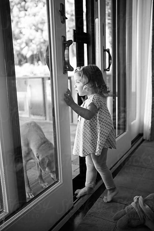 Black & white photograph of toddler on her tip toes opening sliding glass door by Dina Giangregorio for Stocksy United