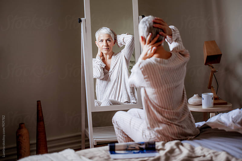 Woman Standing in Front of the Mirror in the Morning by Lumina for Stocksy United