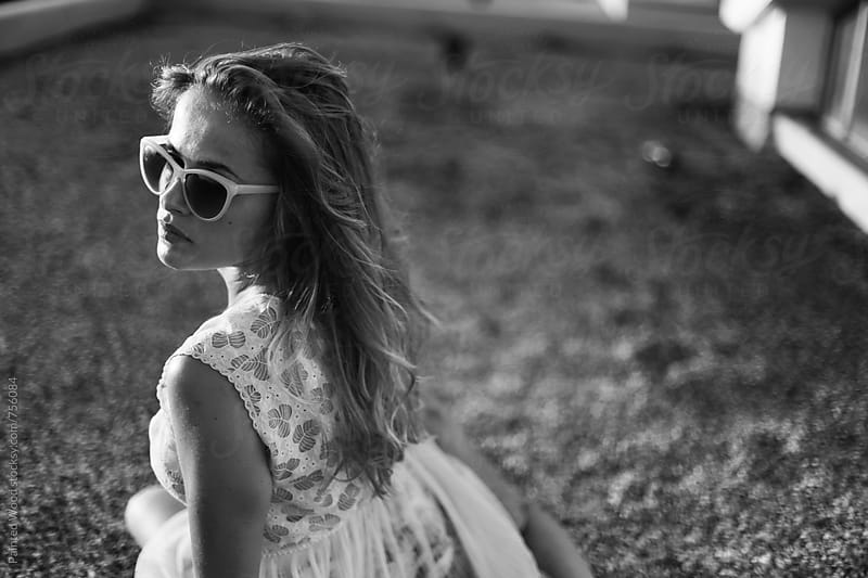 Black and white portrait of a girl with sunglasses in the summer by Painted Wood for Stocksy United