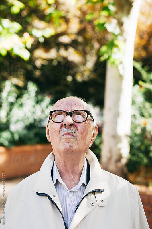 Elderly man looking up standing in the park. by BONNINSTUDIO for Stocksy United