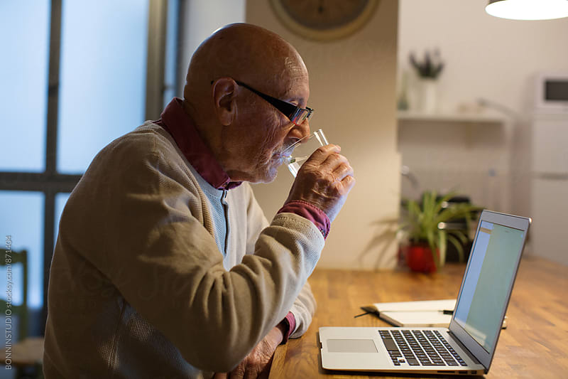 Side view of an elderly man drinking water in the late afternoon. by BONNINSTUDIO for Stocksy United