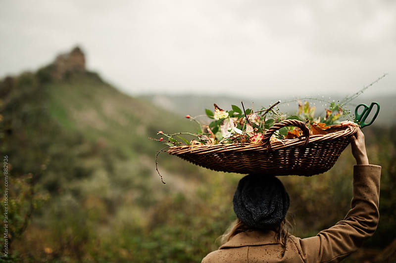 Woman overlooks Tuscan hills with basket of foliage over her head  by Kristen Marie Parker for Stocksy United