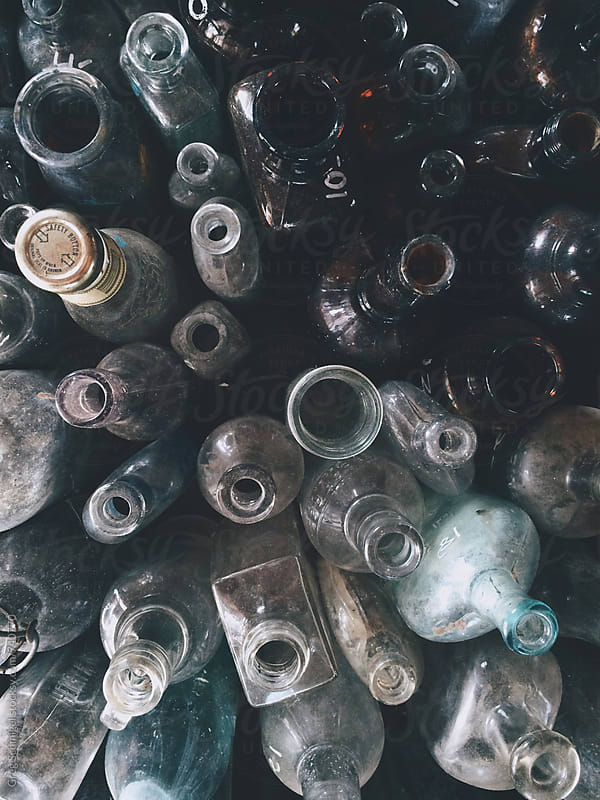 An overhead view of old antique bottles on a wooden table by Greg Schmigel for Stocksy United