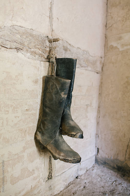 Pair of old boots  hung on stone wall by Zocky for Stocksy United