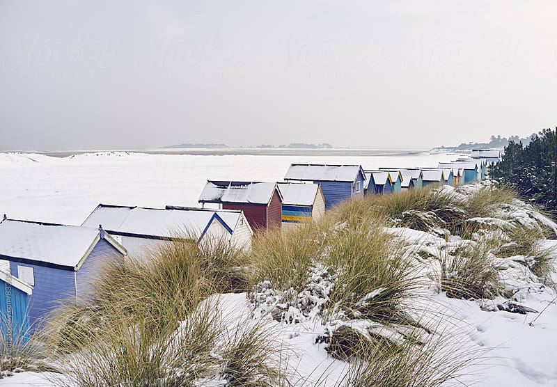 Beach huts and dunes covered in snow at low tide. Wells-next-the-sea, Norfolk, UK. by Liam Grant for Stocksy United