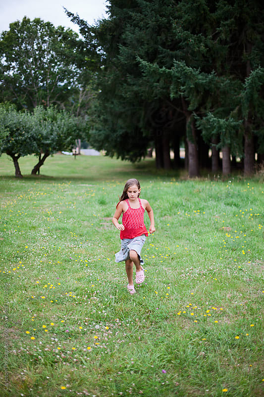 Nine year old girl running on grass with trees behind by Carleton Photography for Stocksy United